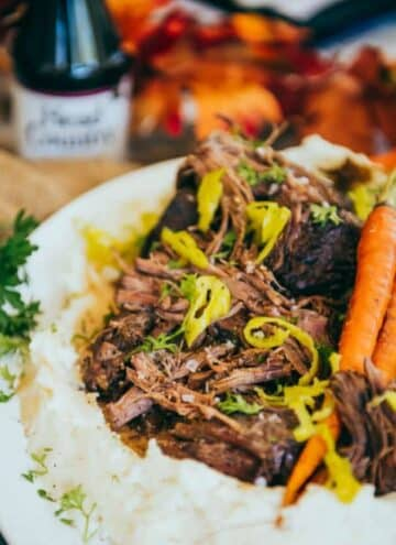 Mississippi pot roast on a bed of mashed potatoes with roasted carrots.
