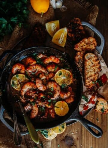 New Orleans BBQ Shrimp in a cast iron skillet with lemon slices and toasted bread around it.