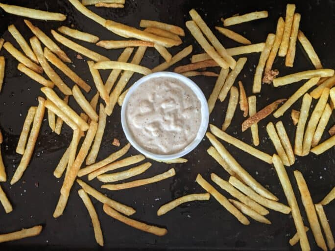 french fries on a platter around umami aioli, mayo mixed with girl carnivore's ooomami powder
