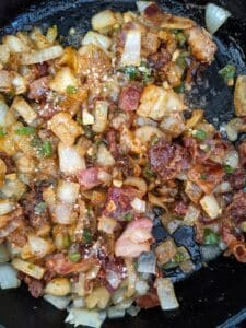showing spices in skillet with sauteed veggies and bacon for sloppy joes