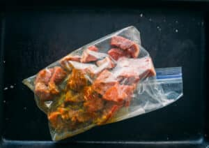 showing steak cut into cubes and marinating in resealable bag