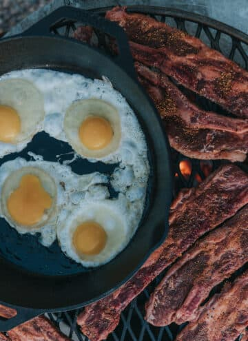 short ribs on a grilling grate over coals with a cast iron skilled filled with eggs