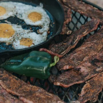 fire grate over the fire filled with cast iron filled with fried eggs, grilled beef, and peppers
