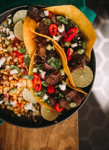 2 fully loaded steak tacos with chopped grilled chuck steak and colorful toppings like peppers, red onion, and cilantro