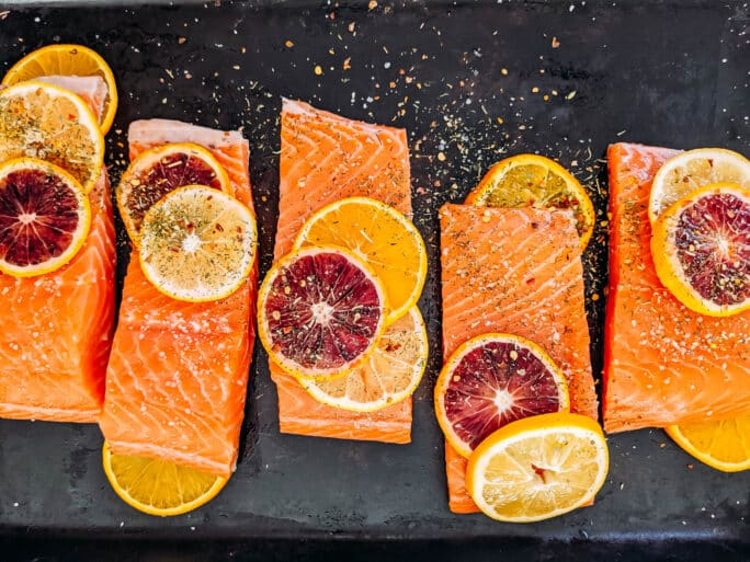 raw salmon on platter with citrus slices and spices sprinkled on top