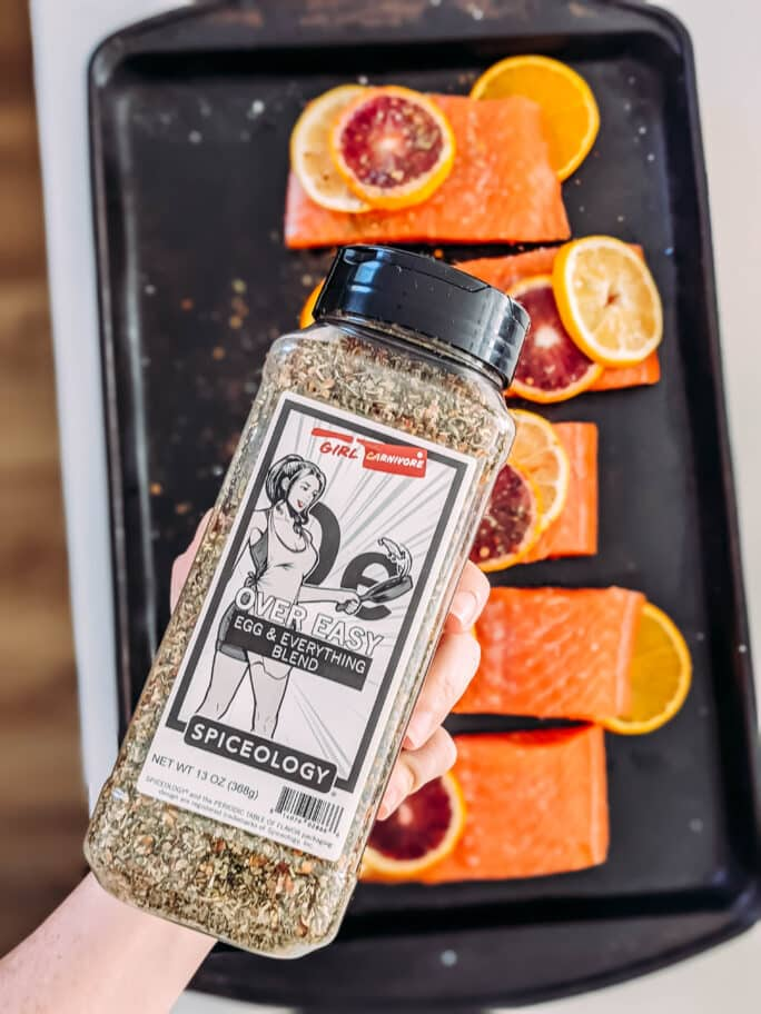 over easy spice blend over raw salmon - showing bottle