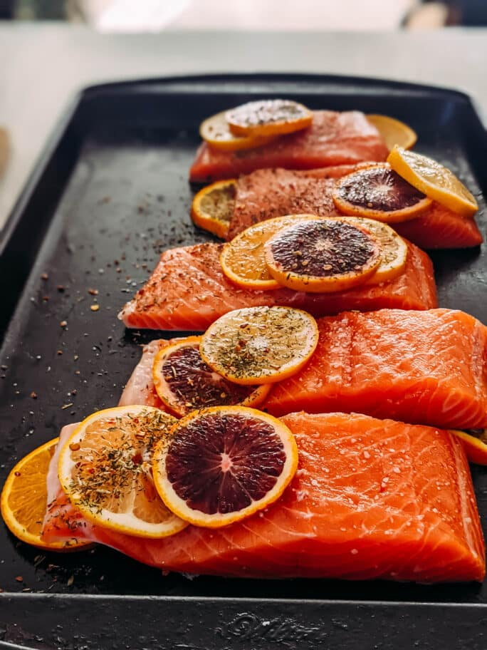 raw salmon assembled on a baking sheet to be cooked with citrus