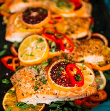 citrus baked salmon topped with sliced sweet peppers and herbs
