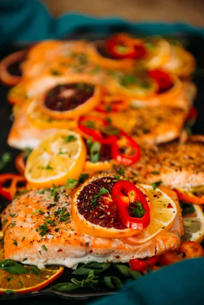 baked salmon topped with bright citrus slices, peppers and herbs