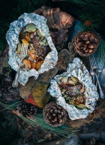 2 garlic steak and potato foil packs opened around a camping scene.