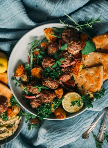 above shot of bowl filled with lamb meatballs, garnished with fresh herbs and lemon served with roasted potatoes and pita
