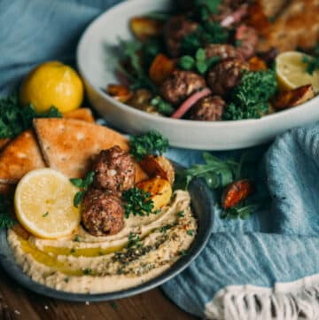 lamb meatballs on a plate with hummus and pita, lemon wedges and herbs for garnish