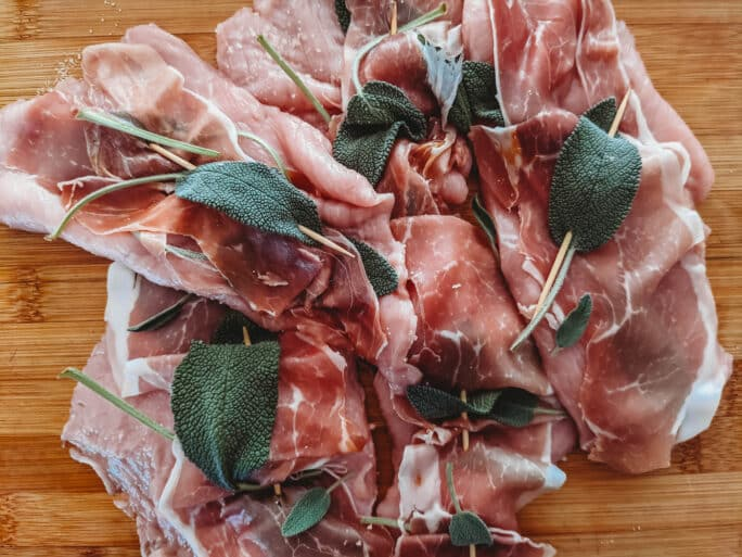 veal prepped for saltimobcca, lined with prosciutto and sage affixed with a toothpicks