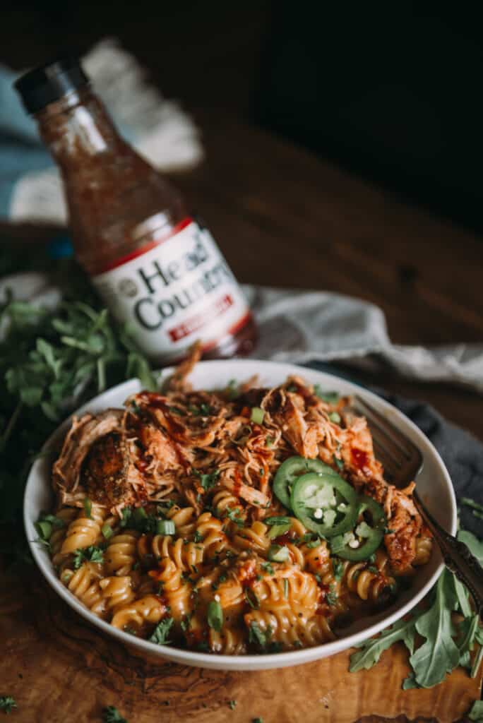 bowl of creamy shredded bbq chicken mac and cheese with bottle of head country bbq sauce behind