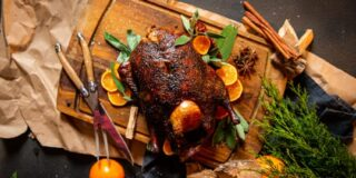 smoked duck on platter with sage and sliced oranges